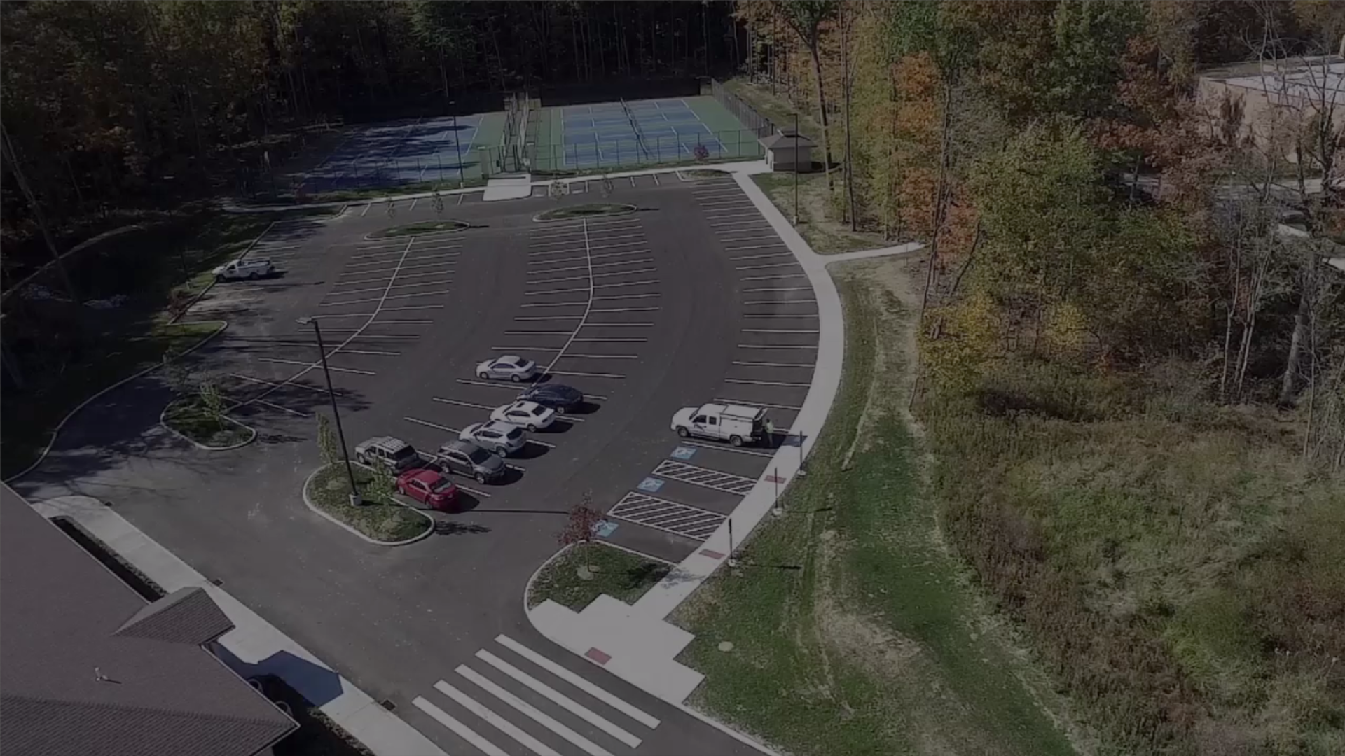 aerial view of parking lot next to blue tennis courts